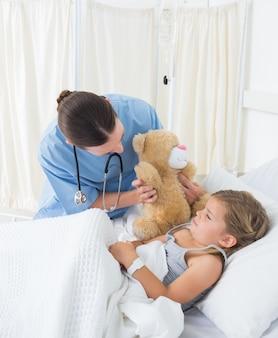 Arts met teddybeer vermakelijk ziek meisje