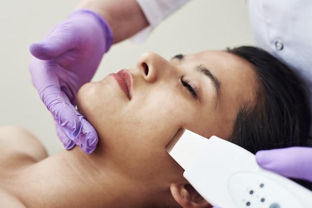 Arts met ultrasone scraber. jonge vrouw die reinigingstherapie ontvangt