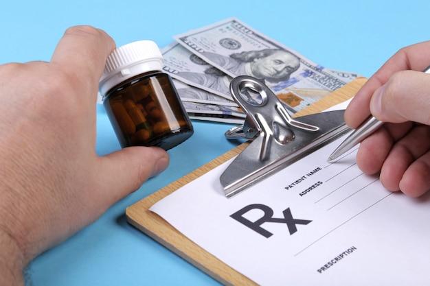 Arts of apotheker pot of fles pillen in de hand houden op een achtergrond van dollars bankbiljetten en het schrijven van een recept op een speciaal formulier. medische kosten en gezondheidszorg betaling concept.