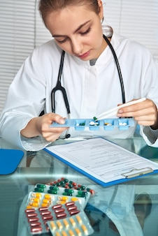 Arts of verpleegkundige in witte jas selecteert pillen voor een patiënt che