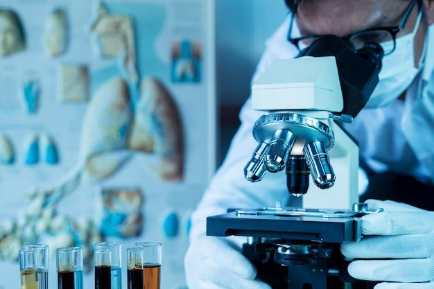 Arts of wetenschapper draagt een medisch gezichtsmasker en kijkt in de microscoop tijdens het werken aan medisch onderzoek in het covid-19- of coronaviruslaboratorium