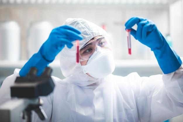 Arts of wetenschapper-onderzoeker die in laboratorium werkt dat een spuit met vloeibare virusvaccins houdt