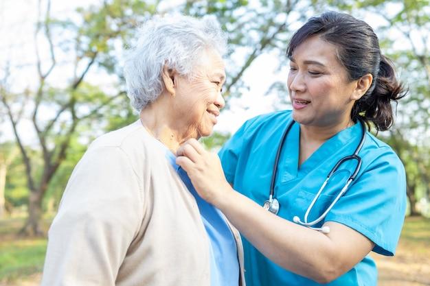 Arts ondersteuning senior vrouw patiënt in park.