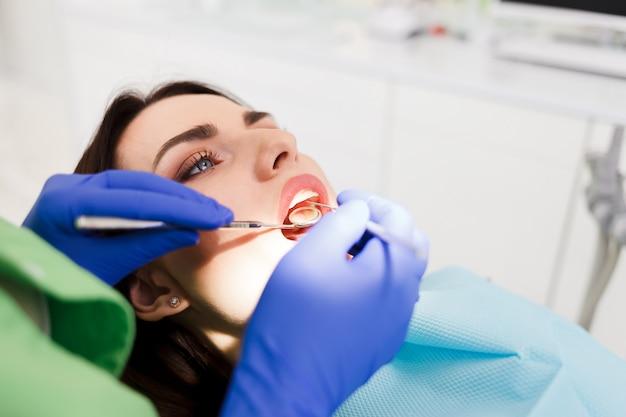Arts onderzoekt de mondholte van de patiënt. de vrouw behandelt tandenclose-up bij de tandkliniek