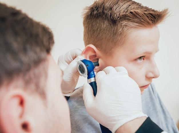 Arts onderzoekt jongensoor met otoscoop. medische apparatuur.
