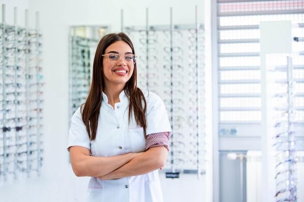 Arts-oogarts staat in de buurt van planken met verschillende brillen