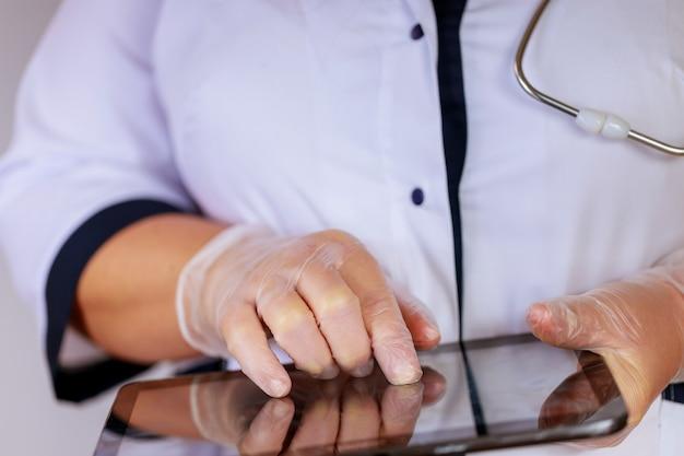 Arts op het werken met behulp van digitale tablet aan balie in kliniek, geneeskunde voor de gezondheidszorg