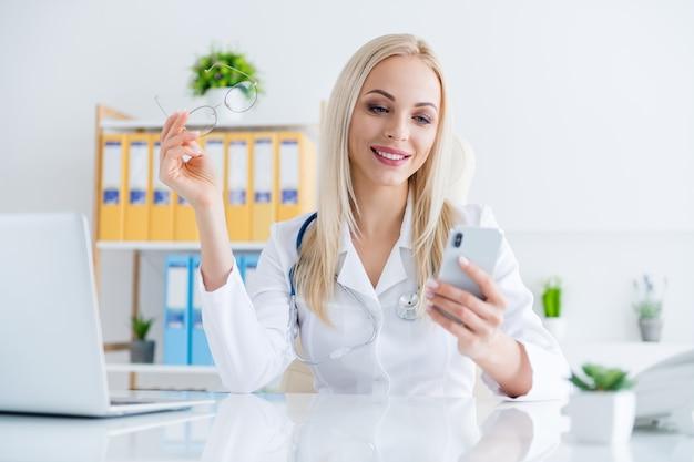 Arts op zoek op telefoon in haar kantoor