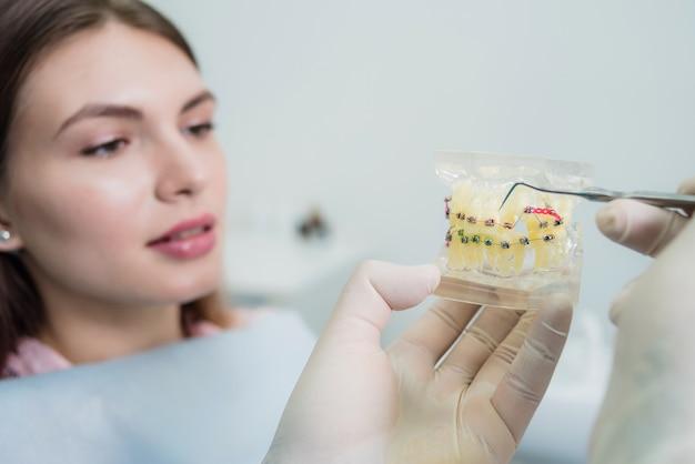 Arts-orthodontist legt de patiënt uit hoe de beugels zijn gerangschikt