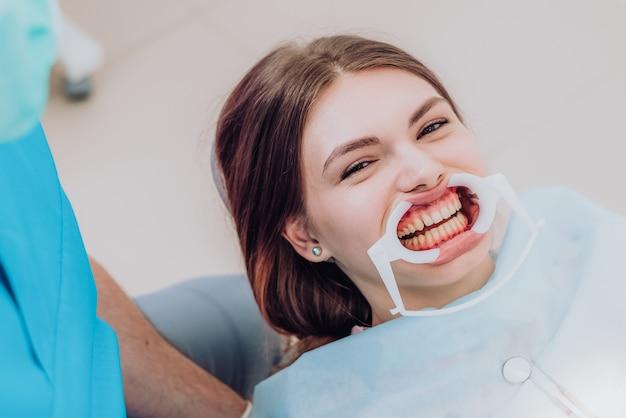 Arts-orthodontist voert een procedure uit voor het reinigen van tanden