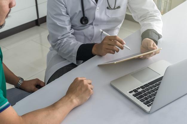 Arts overlegt met de patiënt over zijn gezondheid op een bureau