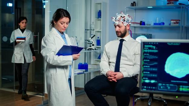 Arts praat over ziektesymptomen tijdens onderzoeken met behulp van high-tech hersengolf scanning headset