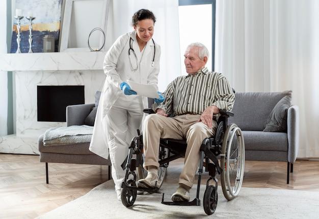 Arts praten met senior man binnenshuis