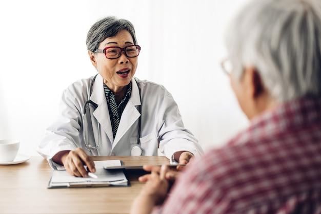 Arts raadplegen en controleren van informatie met senior vrouw in het ziekenhuis