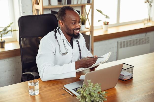 Arts raadplegen voor patiënt, het geven van aanbeveling. afro-amerikaanse arts tijdens zijn werk met patiënten, recepten voor medicijnen uitleggend. dagelijks hard werken voor de gezondheid en het redden van levens tijdens de epidemie.