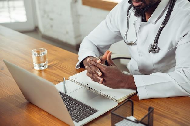 Arts raadplegen voor patiënt, werken met laptop. afro-amerikaanse arts tijdens zijn werk met patiënten, recepten voor medicijnen uitleggend. dagelijks hard werken voor de gezondheid en het redden van levens tijdens de epidemie.