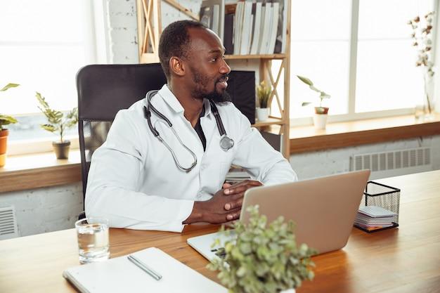Arts raadplegen voor patiënt, werken met laptop. afro-amerikaanse arts tijdens zijn werk met patiënten, uitleg over recepten voor medicijnen. dagelijks hard werken voor de gezondheid en het redden van levens tijdens de epidemie.