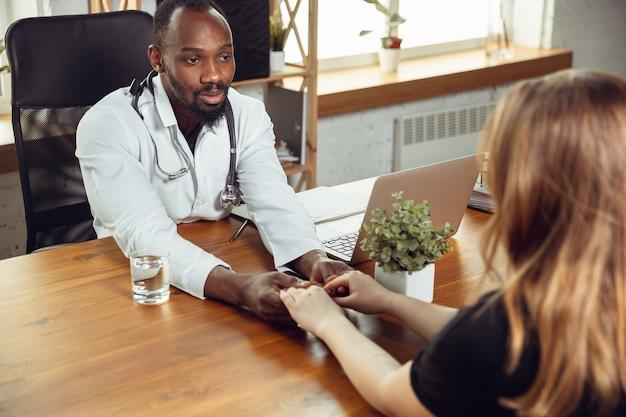 Arts raadplegen voor vrouwelijke patiënt in kabinet. afro-amerikaanse arts tijdens zijn werk met patiënten, recepten voor medicijnen uitleggend. dagelijks hard werken voor de gezondheid en het redden van levens tijdens de epidemie.