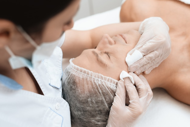Arts reinigt de huid van de mens. de man ligt op de bank.