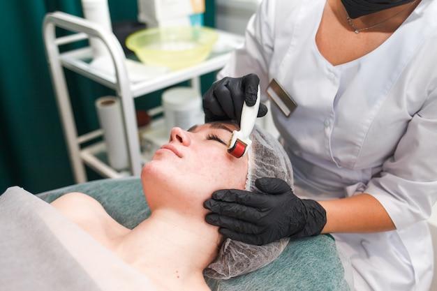 Arts-schoonheidsspecialist maakt een gezichtsmassage met een dermo-roller. vrouw in schoonheidssalon tijdens mesotherapie procedure met mesoscooter