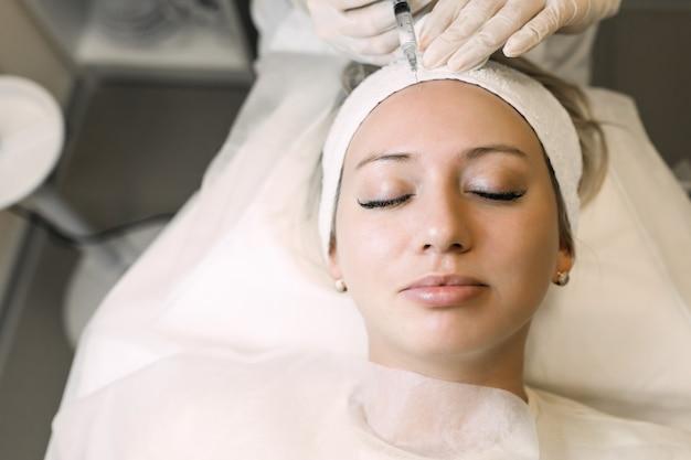 Arts schoonheidsspecialist maakt een injectie van medicijnen in het voorhoofd van een vrouwelijke patiënt