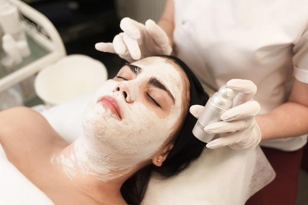 Arts-schoonheidsspecialist maakt een voedend masker voor het gezicht en houdt een potje crème in zijn handen