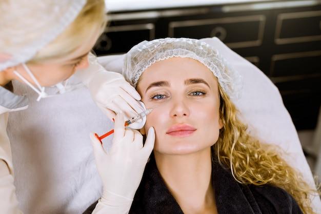 Arts-schoonheidsspecialist voert de verjongende procedure voor gezichtsinjecties uit om rimpels op de gezichtshuid van een mooie, jonge vrouw in een schoonheidssalon aan te halen en glad te strijken.