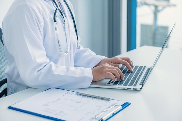 Arts sms't naar laptop en registreert resultaten van gezondheidsonderzoek en medicatiegebruik van patiënt