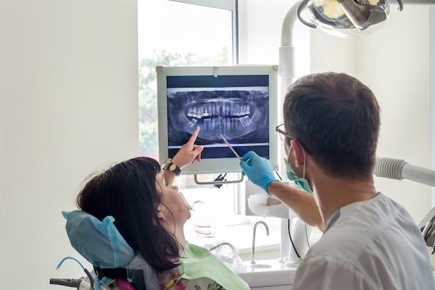 Arts-tandarts wijzend op patiënten xray op monitor