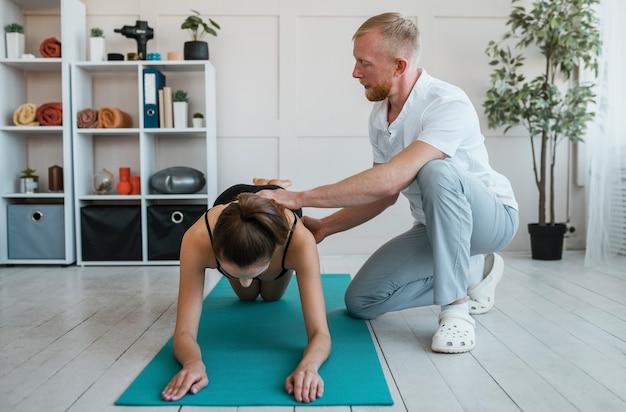 Arts tijdens een fysiotherapie-sessie met vrouwelijke patiënt