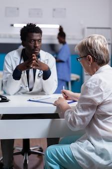 Arts van afrikaanse etniciteit die oudere patiënt raadpleegt