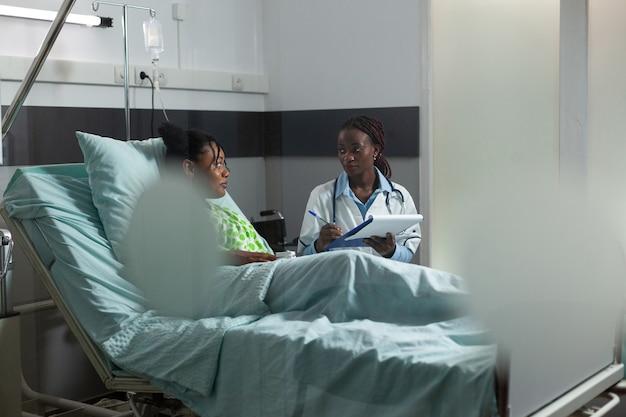 Arts van afrikaanse etniciteit die ziekteadvies geeft aan tiener die in ziekenhuisbed in de kliniek zit. afro-amerikaanse doktersvrouw helpt jonge vrouw, patiënt met ziektebehandeling