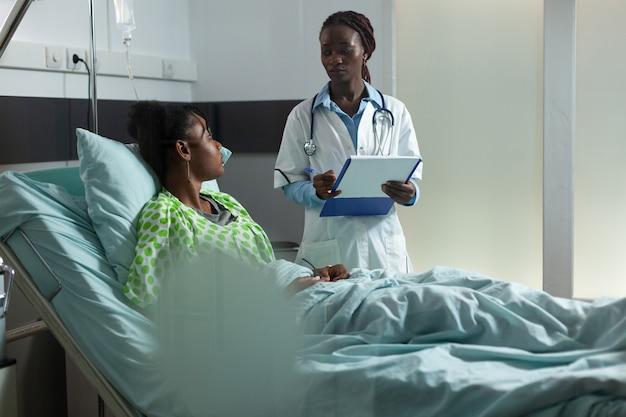 Arts van afro-amerikaanse etniciteit die jonge patiënt raadpleegt over het genezingsproces in de ziekenhuisafdeling. gespecialiseerde vrouw praat met meisje dat in bed zit met medische apparatuur