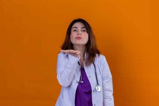 Arts van middelbare leeftijd die witte laag draagt en met stethoscoop de camera bekijkt die een kus blaast die met hand op lucht mooi over geïsoleerde oranje muur is