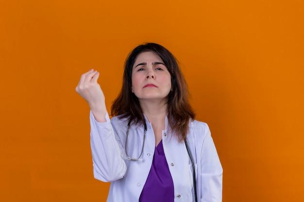 Arts van middelbare leeftijd die witte laag draagt en met stethoscoop het gesturing met opgeheven hand die italiaans gebaar over geïsoleerde oranje muur doet