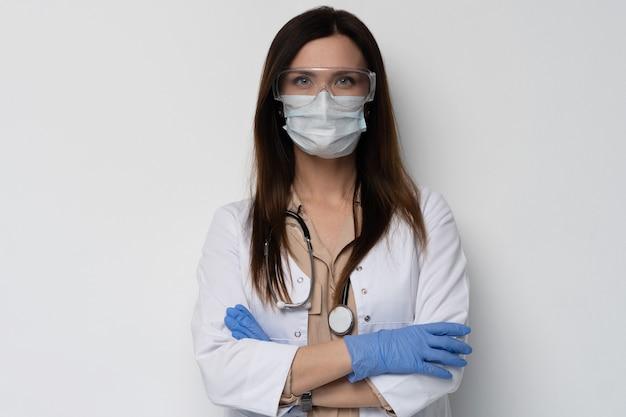 Arts / verpleegster die achter chirurgmasker glimlachen. het close-upportret van het jonge kaukasische vrouwenmodel in witte medische schrobt en wegwerphandschoenen