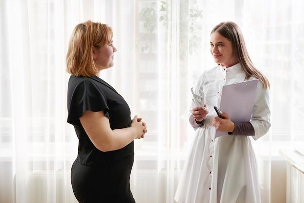 Arts-voedingsdeskundige, diëtist en vrouwelijke patiënt op overleg op kantoor. jonge lachend