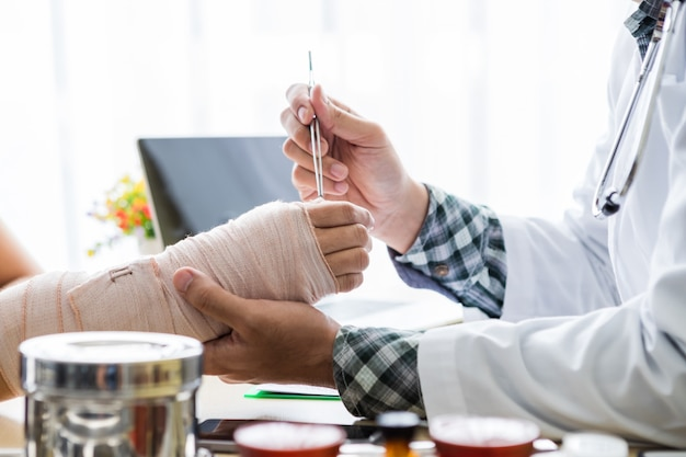 Arts voor het controleren van de arm van de vrouwelijke patiënthand vanwege haar gebroken arm