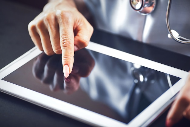 Arts vrouw glimlach greep tablet pc, met behulp van computer.