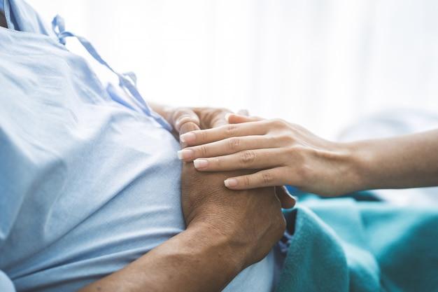 Arts wat betreft handen aan aanmoediging geestelijk van bejaarde patiënt na chirurgie bij bed in het ziekenhuis.