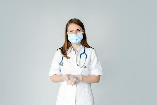 Arts wearing medical mask en geïsoleerde handschoenen