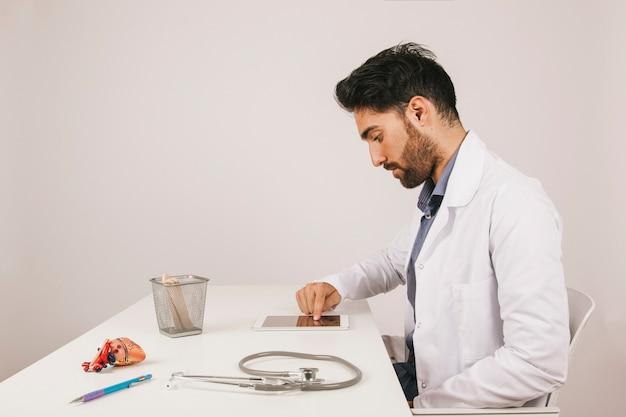 Arts werken met tablet in het kantoor