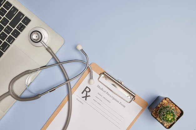 Arts werkplek. bovenaanzicht van het kantoor van de dokter met stethoscoop, laptop, pen en klembord met kopie ruimte voor uw tekst. moderne medische informatietechnologie. plat leggen, kopieer ruimte.