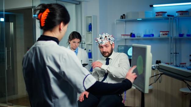 Arts wijzend op computermonitor met touchscreen testen van fysieke reacties en zenuwstelsel van man met hersengolf scanning headset in technologisch geavanceerd laboratorium