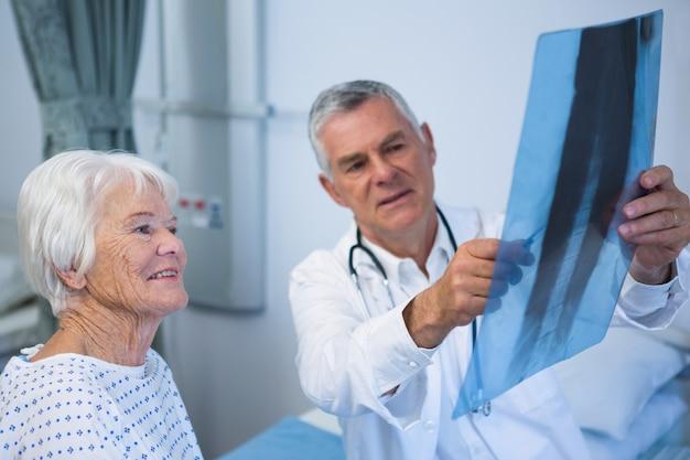 Arts x-ray rapport bespreken met senior patiënt