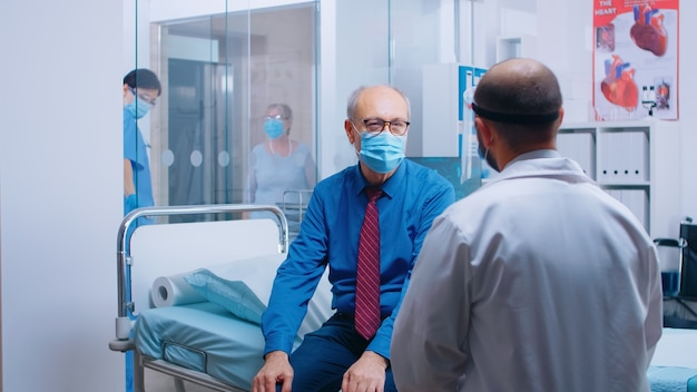 Arts ziekenhuis medisch consult tijdens covid-19 wereldwijde pandemie. oude gepensioneerde senior man met een masker en gezondheidswerker in beschermende uitrusting voor overleg. moderne privékliniek