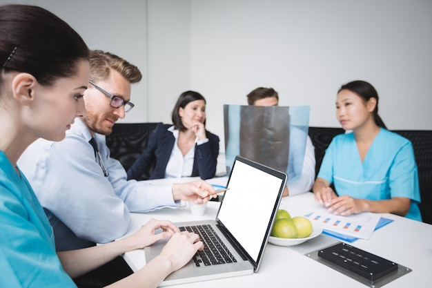 Artsen bespreken over laptop tijdens vergadering