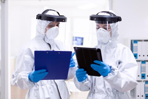 Artsen die aantekeningen maken met pbm-pak en gezichtsmasker in ziekenhuis medische collega's die professionele uitrusting dragen tegen infectie met coronavirus als veiligheidsvoorzorgsmaatregel.