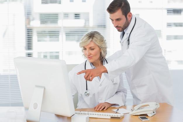 Artsen die computer met behulp van op medisch kantoor