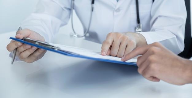 Artsen die de resultaten van het gezondheidsonderzoek met de hand wijzen, rapporteren en bevelen medicatie aan patiënten aan.